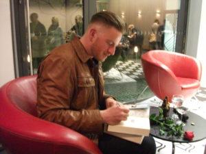 """Szczepan Twardoch signiert sein Buch """"Drach"""" Foto: Manuela Leibig"""